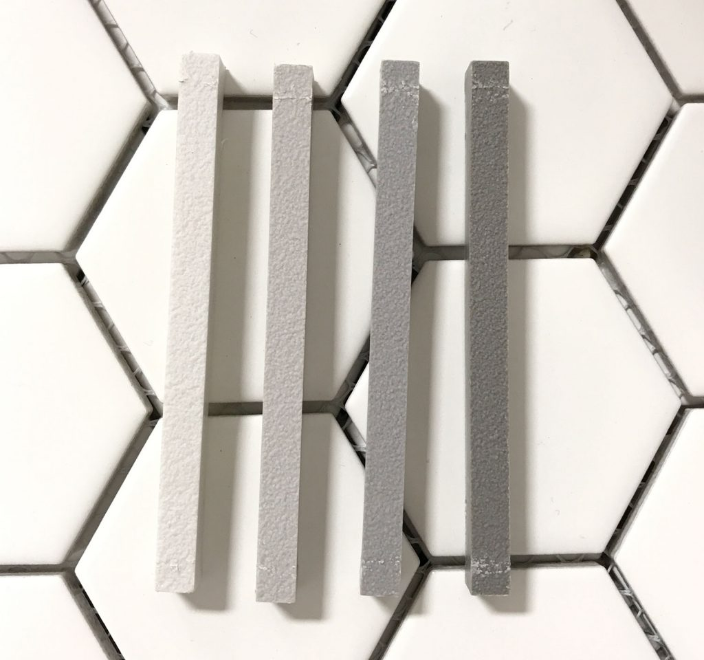 four mapei grout sample sticks atop white hex tile going from light to dark