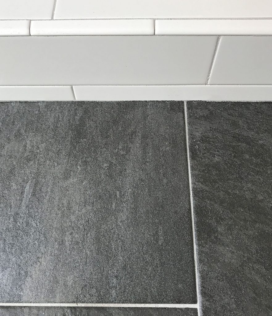white subway tile shower next to dark slate floor with same gray grout