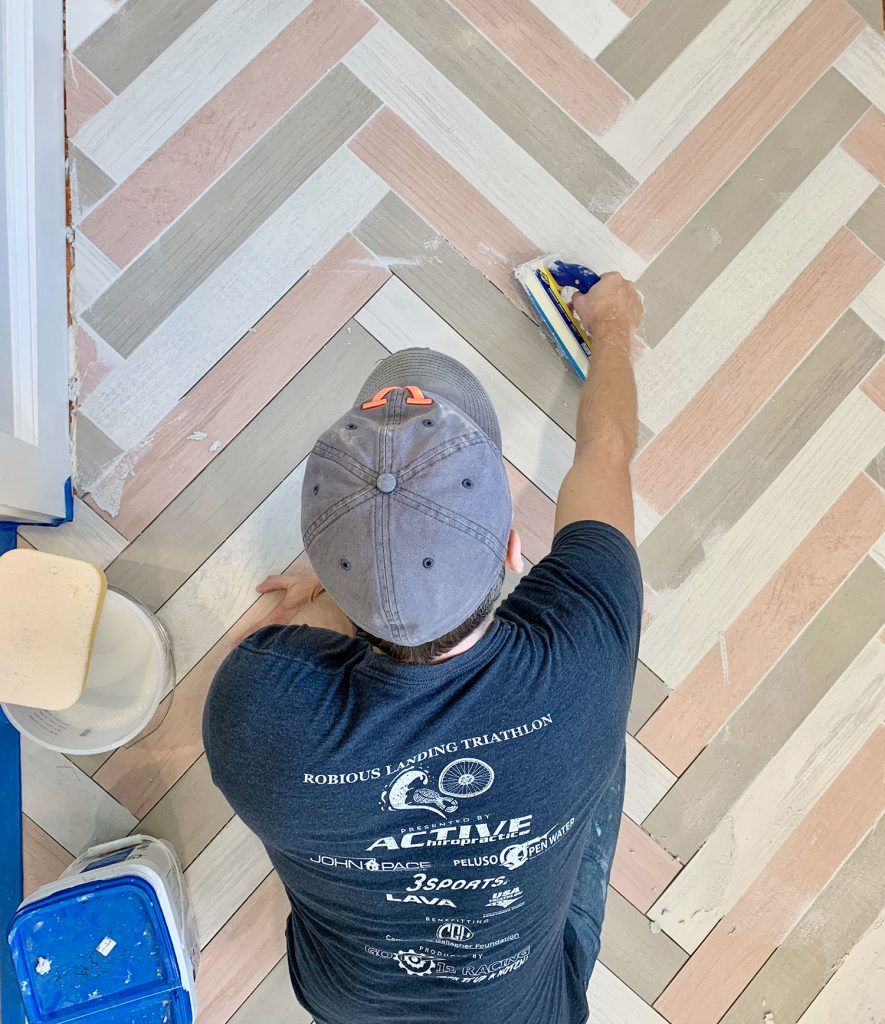John grouting a colorful herringbone mudroom floor with mapei grout