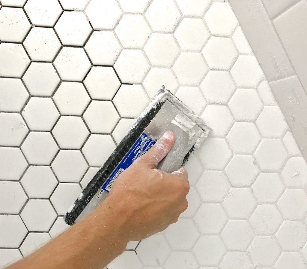 Spreading grout into white hex tile with grout float