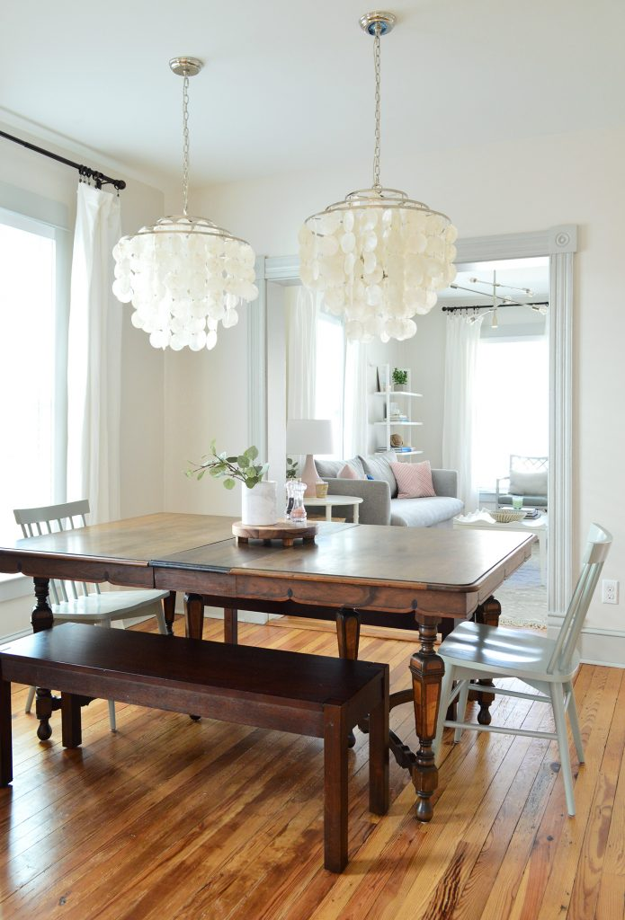 vintage dining table with two capiz chandeliers over top