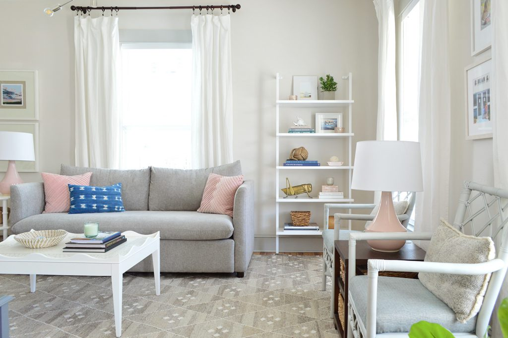 white heron walls in beach house living room with gray sofa and tall bookcase