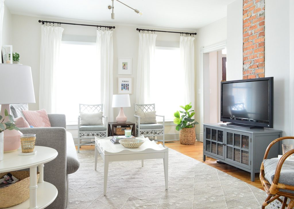 TV in gray neutral bright living room against exposed brick chimney
