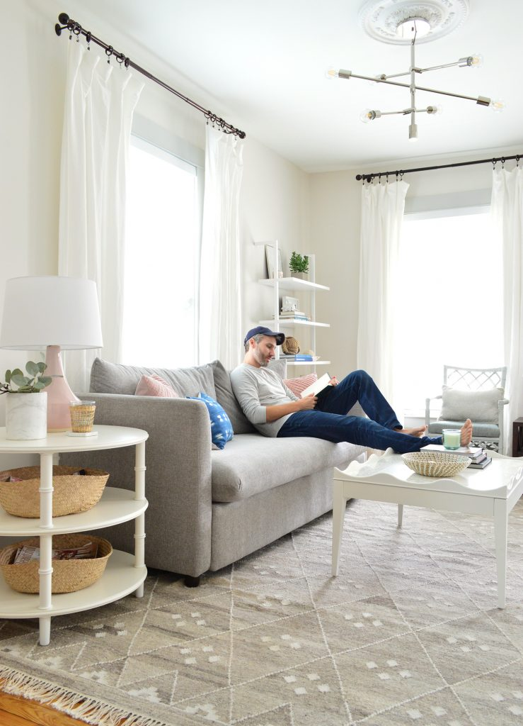 John reading on gray sofa with feet on scalloped white coffee table