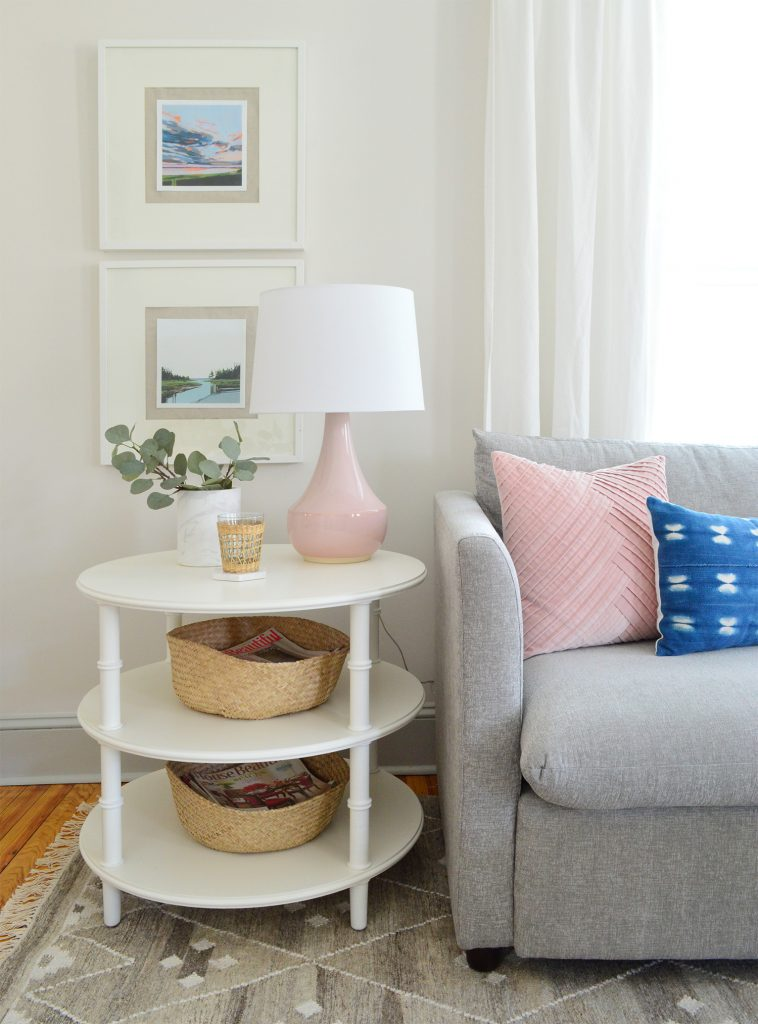 round white three tiered bamboo side table with pink lamp and gray sofa