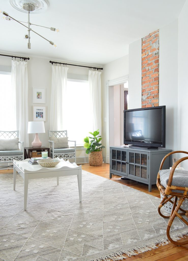 brick chinmey with TV on dark gray media cabinet with neutral furnishings