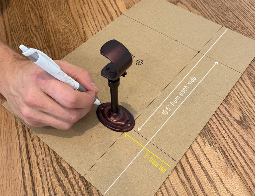 Marking lines on cardboard to make a curtain rod hanging template