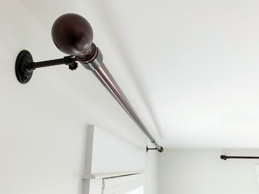 Allen + Roth Bronze curtain rods hung against white wall