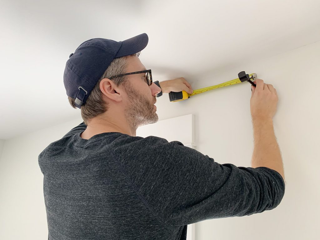 John measuring wall above window while holding curtain rod hook