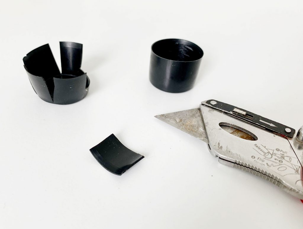 Cut pieces of black plastic to help make curtain rod more level