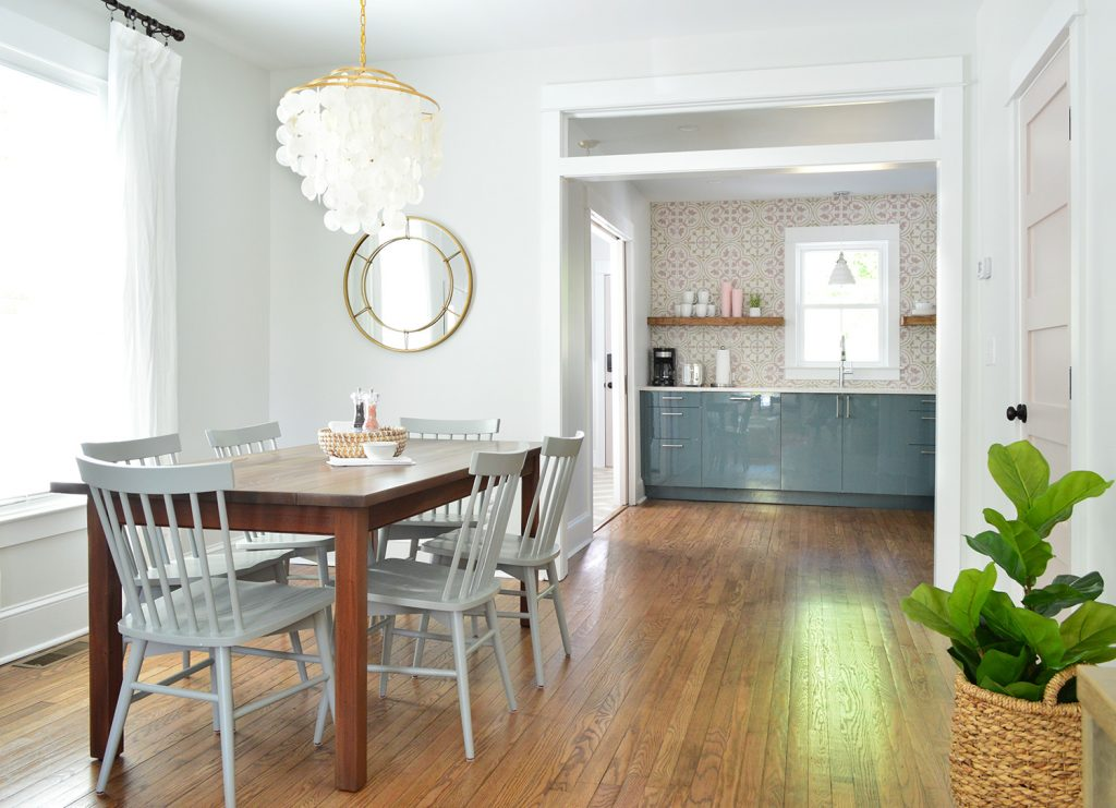 Bright Dining Room With Capiz Chandelier Looking Into Pink And Blue Kitchen