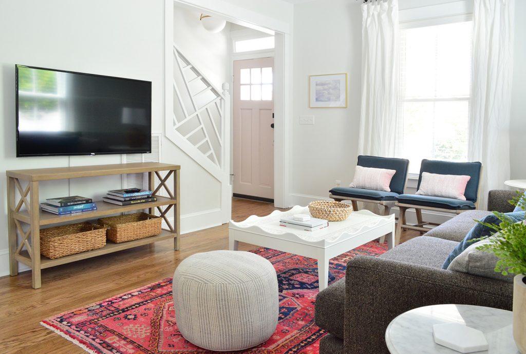 Helles Strandhaus-Wohnzimmer mit Puff und Chippendale-Treppengeländer