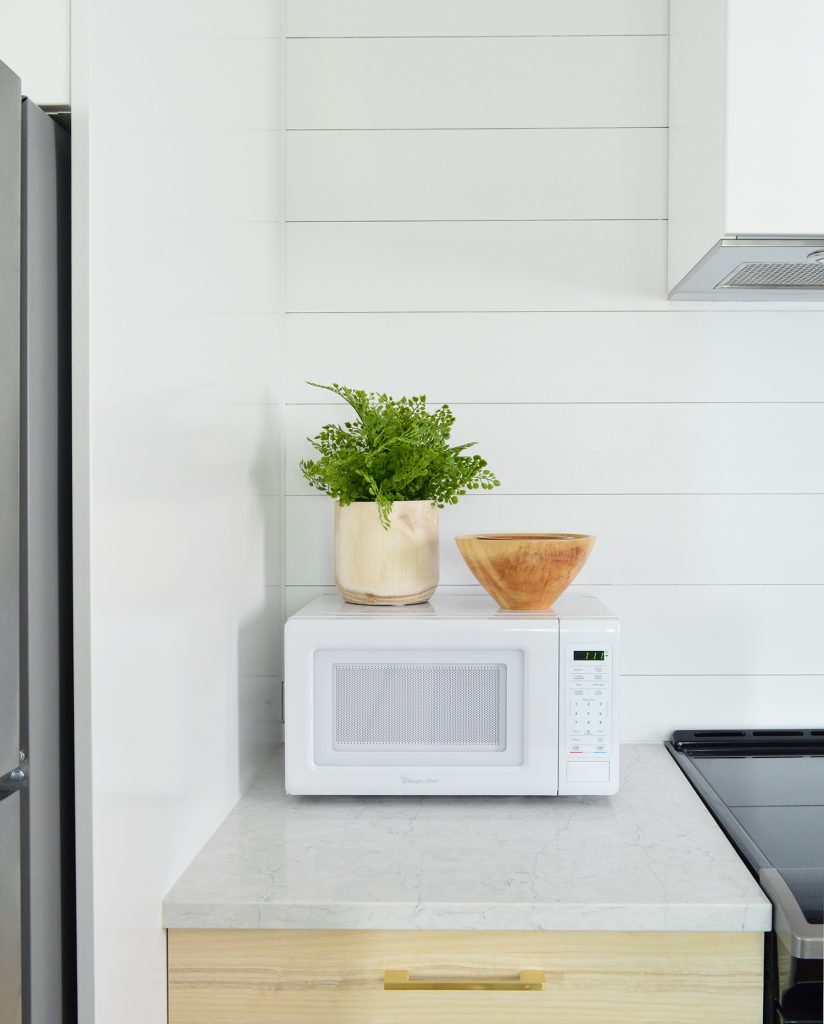 Detail Of Planked Wall In Duplex Kitchen With Counter Microwave