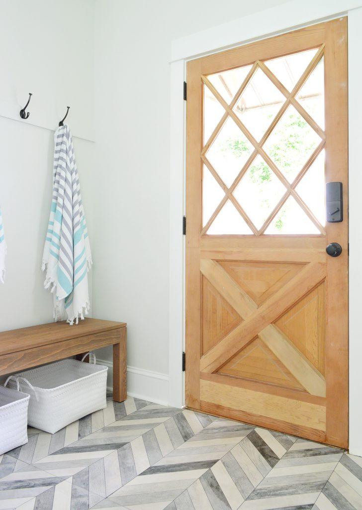 Diamond Paned Wood Door With Bench And Hooks In Duplex Mudroom