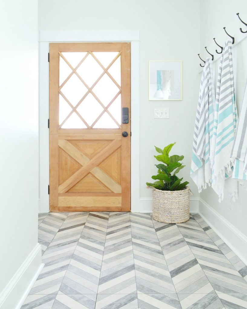 Diamond Paned Wood Door In Duplex Mudroom With Chevron Floor