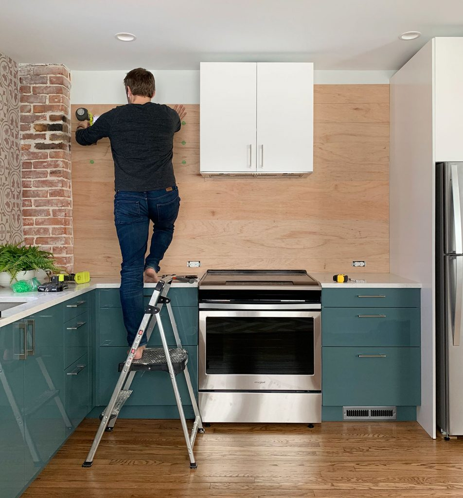 John Standing On Ladder Nailing Wood Paneled Backsplash In Blue Kitchen