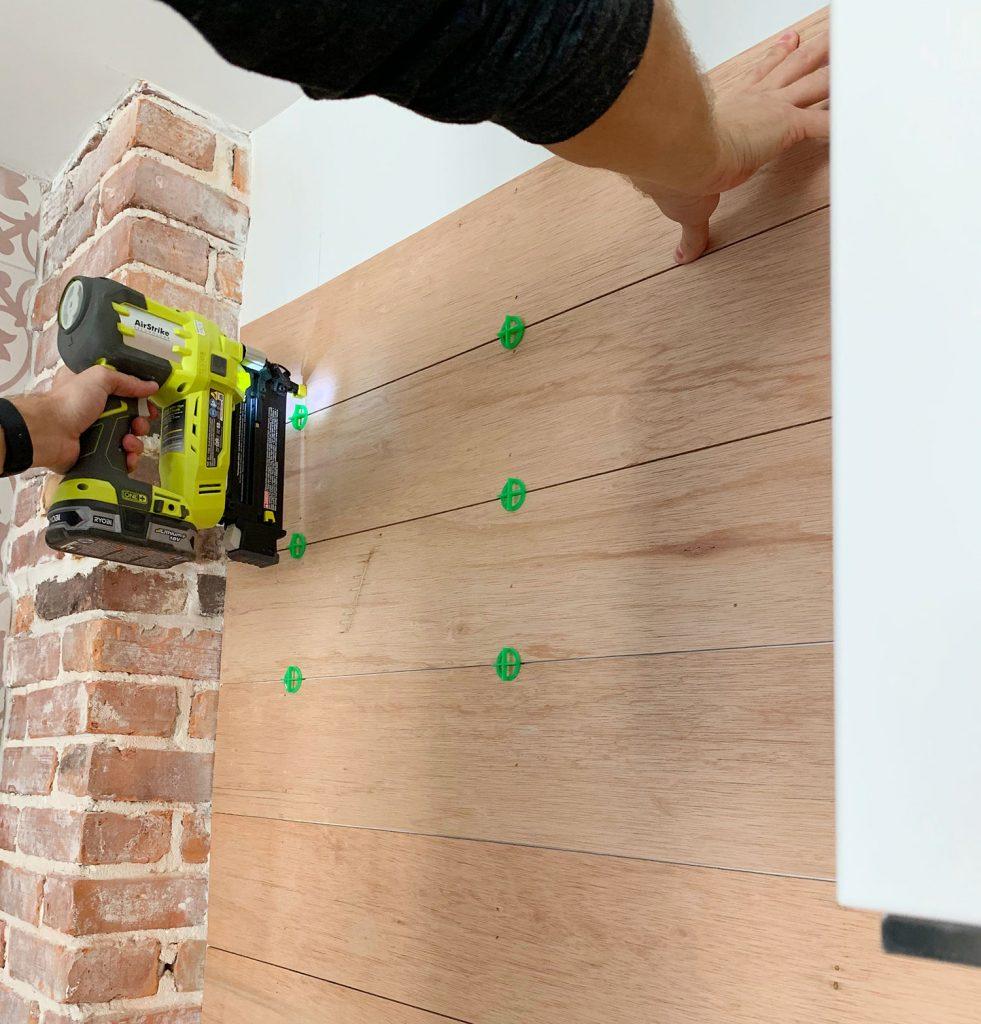 Nail Gun Securing Wood Panels To Backsplash Using Tile Spacers