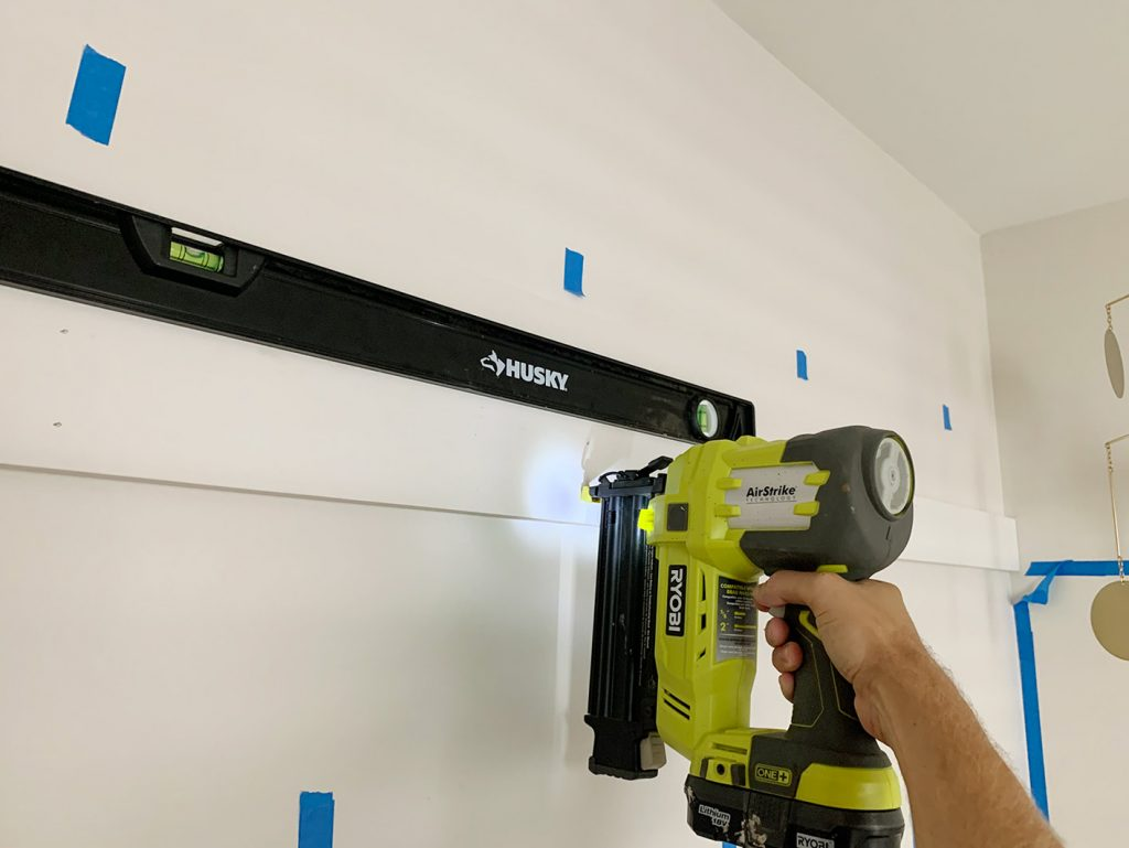 Using Nail Gun To Install Top Rail Of Board And Batten