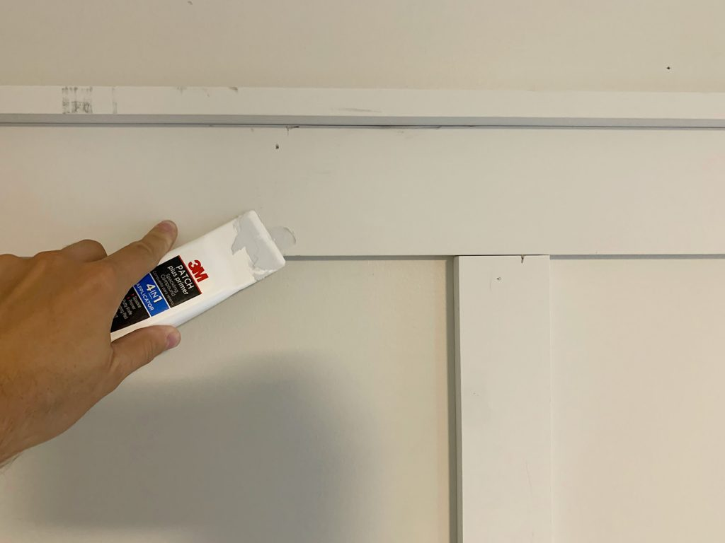 Using Spackling Tool To Fill Nail Holes On Board And Batten