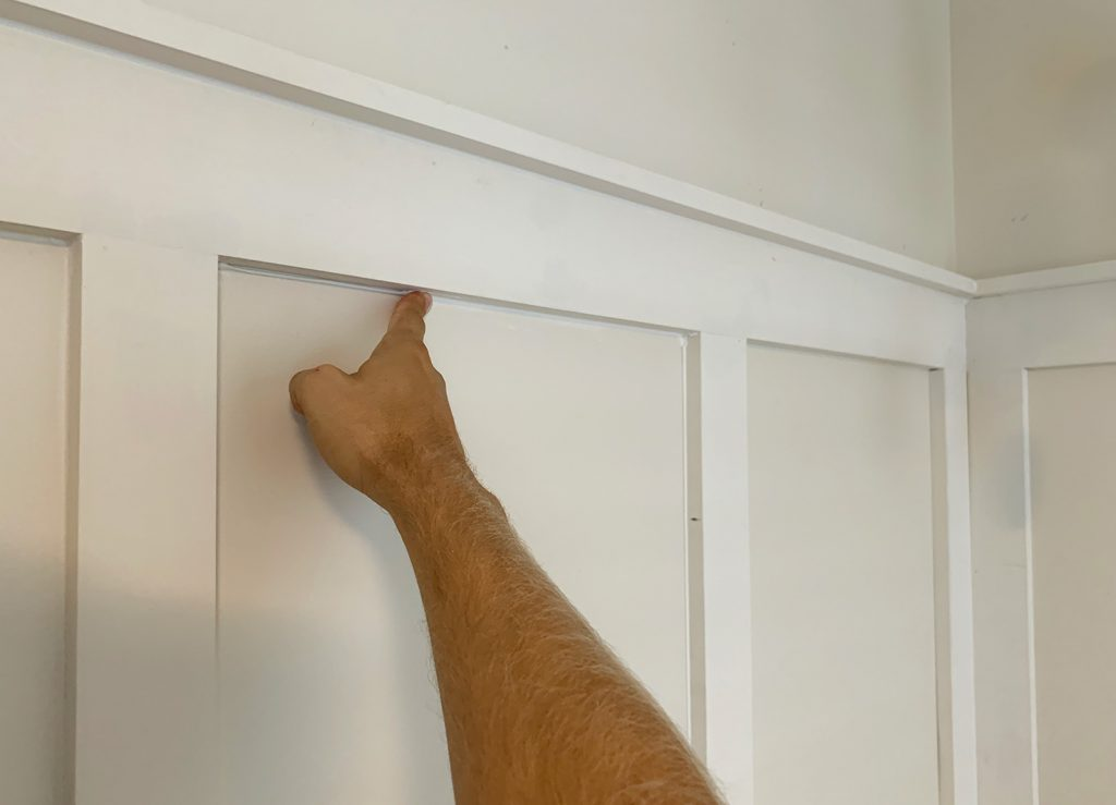Finger Wiping Caulk Smooth Along Seams In Board And Batten