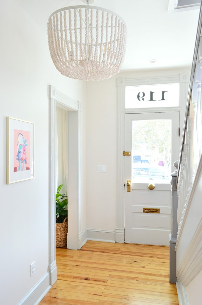 Beaded Chandelier In Beach House Foyer With Glass Front Door And Pink Art