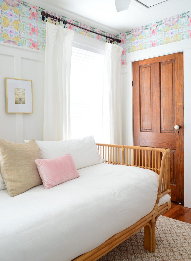 Rattan Daybed mit weißer Bettwäsche im Raum mit hölzernen Türen