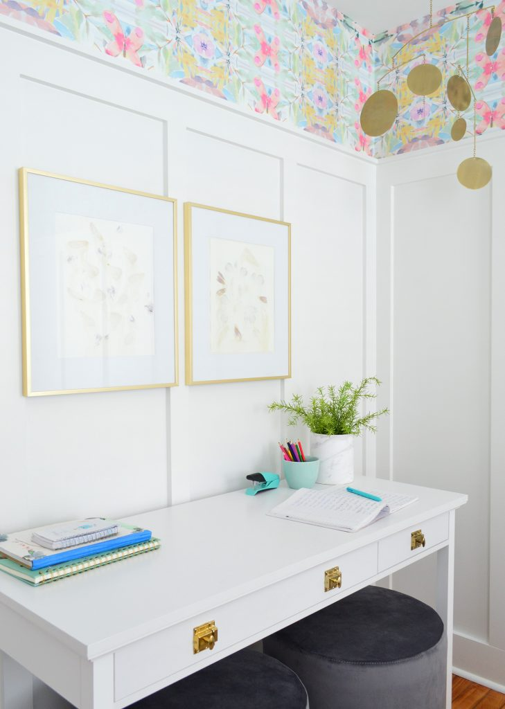 White Desk With Gold Hardware Against Board And Batten With Brass Frames And Mobile