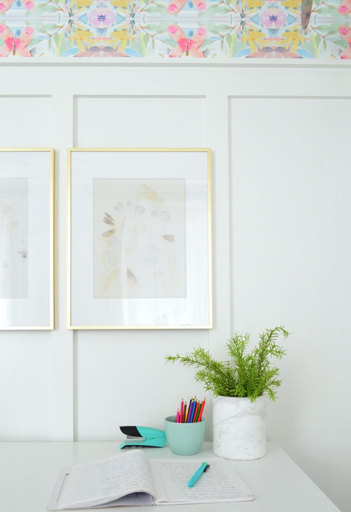 Desk With Gold Frames Hung On Board And Batten