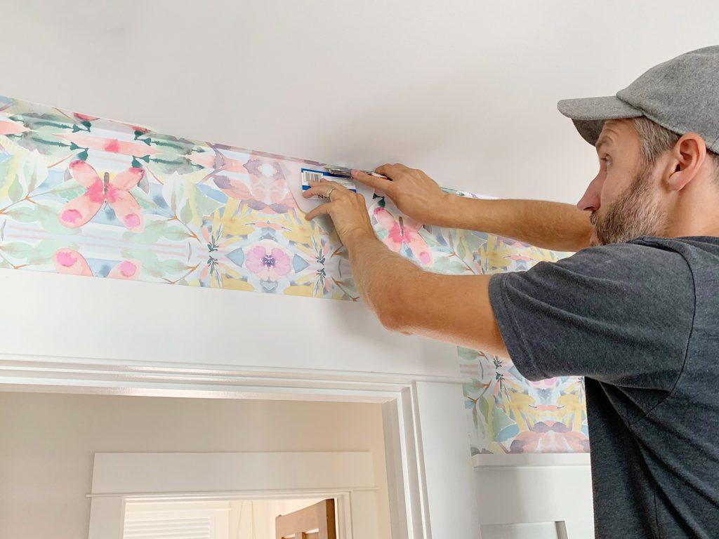 Schneiden von überschüssigem Peel und Stick Wallpaper gegen die Decke mit Messer