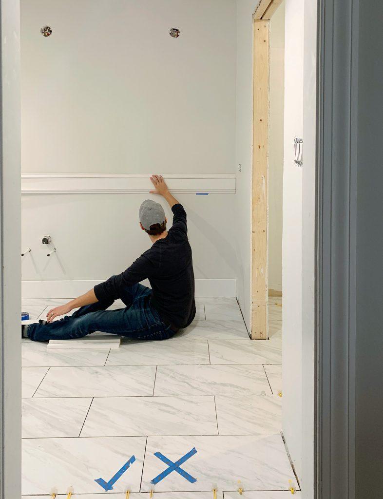 John Holding Test Piece Of Molding In Bathroom