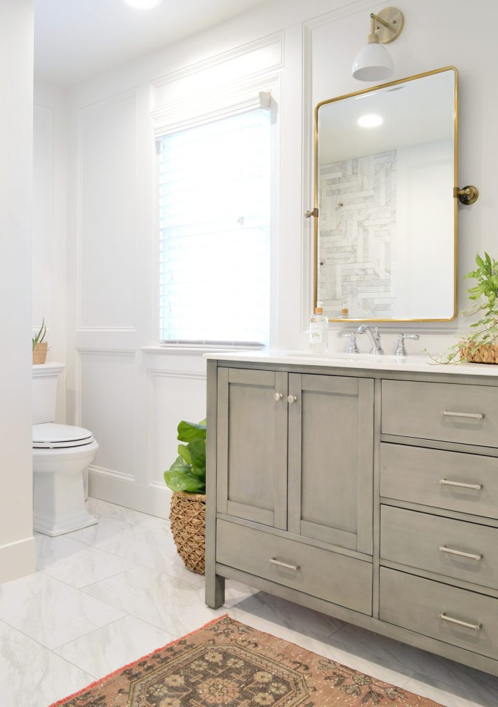 Master Bathroom Update With Gray Vanity Installed With Brass Mirror