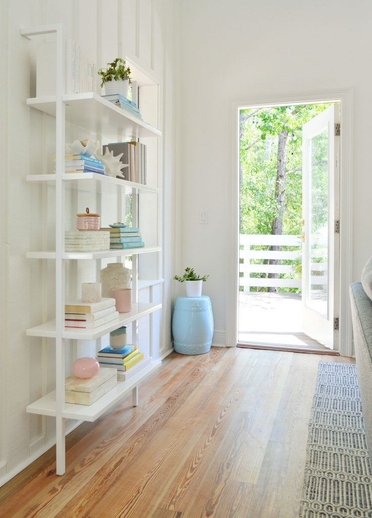 Floating White Bookcase With Door Open To Deck