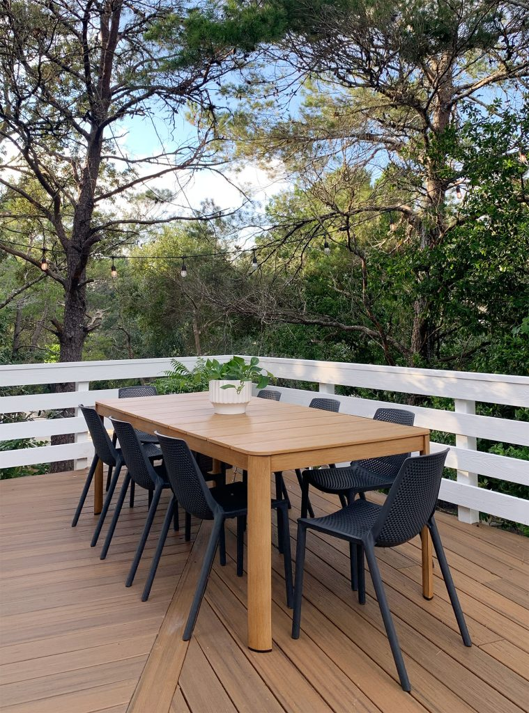 Faux Wood Metal Outdoor Dining Table With Black Chairs Surrounded By Trees