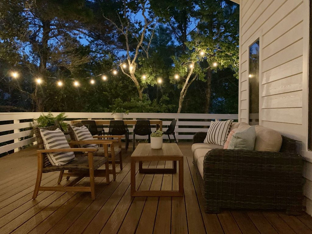Nighttime View Of Outdoor Deck Seating Area With String Lights