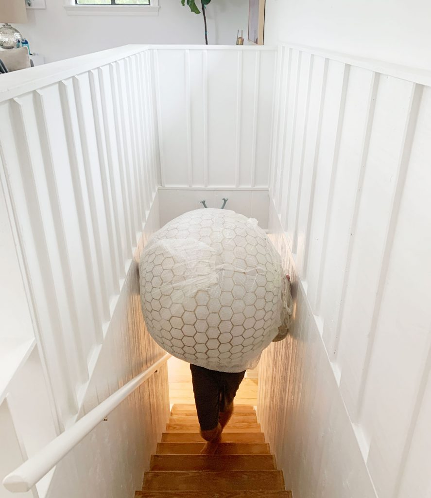 Oversized Capiz Globe Light Narrowly Fitting Up Stairs