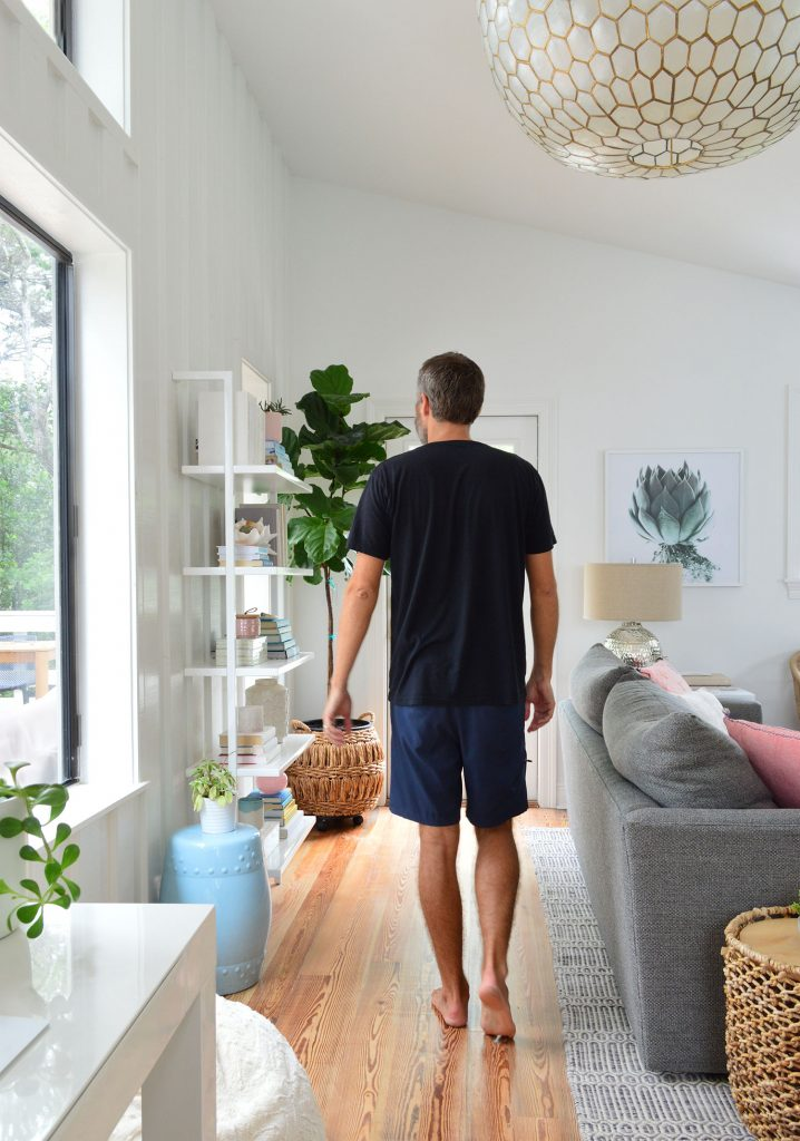 Man In Black Shirt Walking In Living Room Under Large Light Fixture