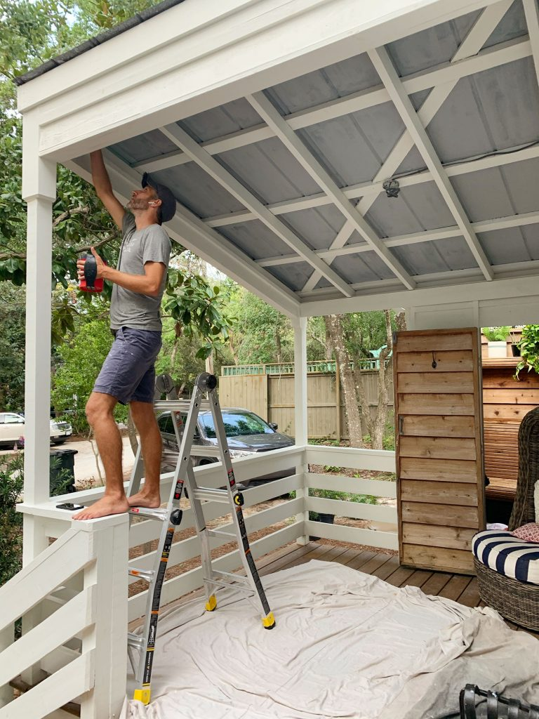 John Standing On Ladder Priming Metal Porch Ceiling