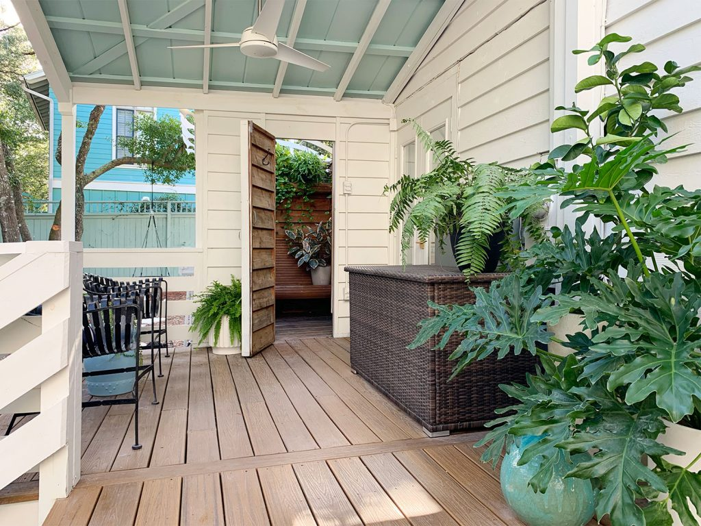 Covered Porch With Blue Ceiling And Open Door To Outdoor Shower