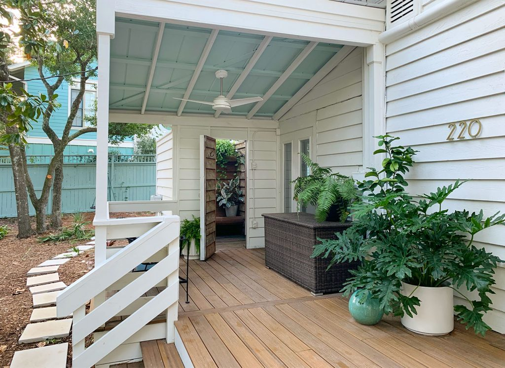 Covered Porch Area With Tropical Plantings Storage Bin And Outdoor Shower