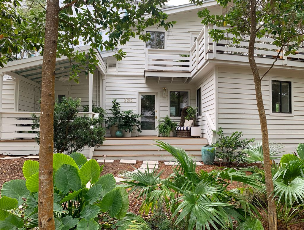 House With White Siding And Tropical Plantings