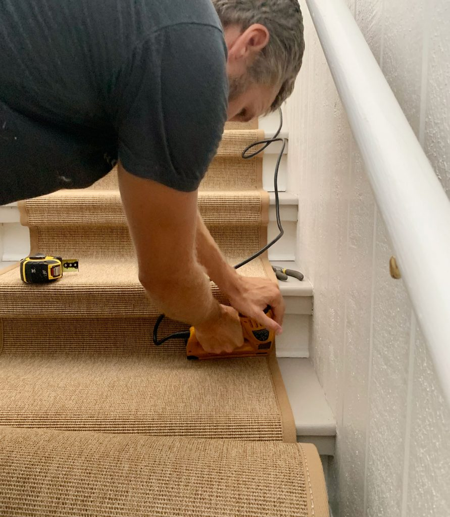 John Using Electric Staple Gun To Drive Staple Into Bottom Corner Of Stair To Secure Sisal Runner