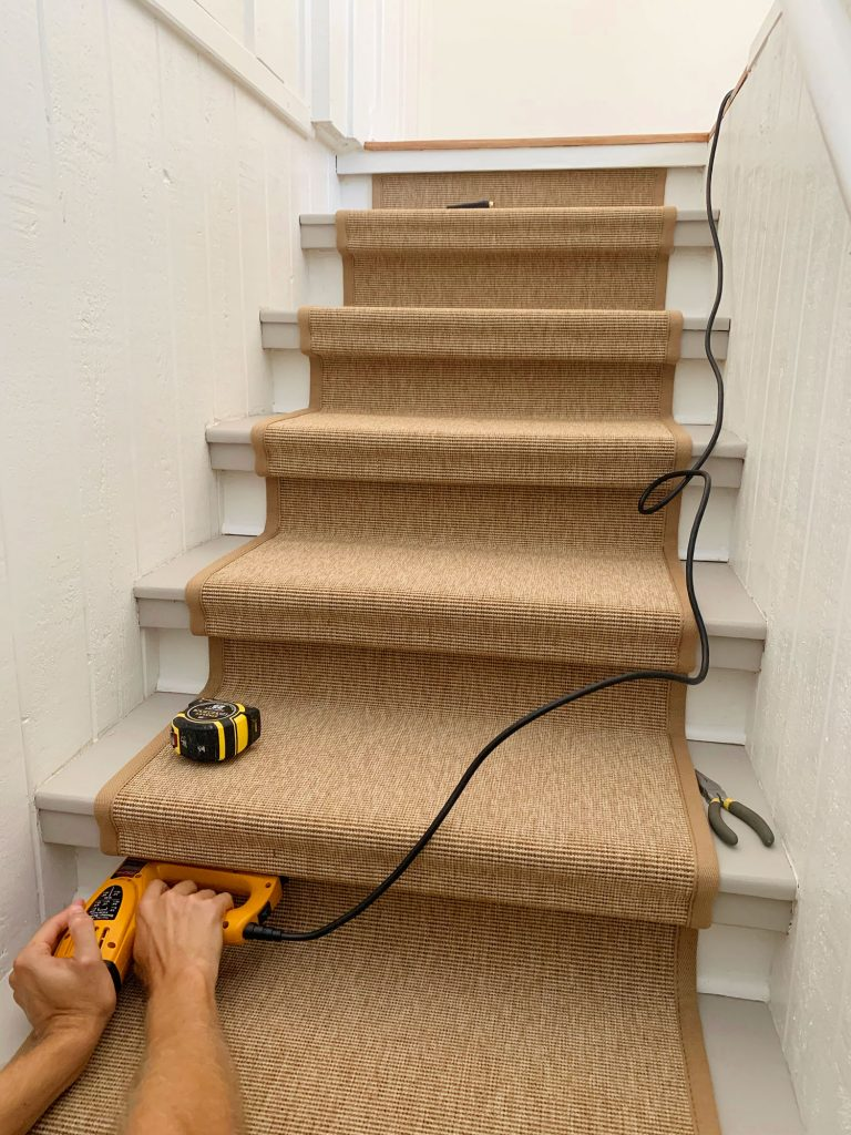 Hand Pushing Electric Stapler Into Underside Of Stair Tread To Secure Sisal Runner