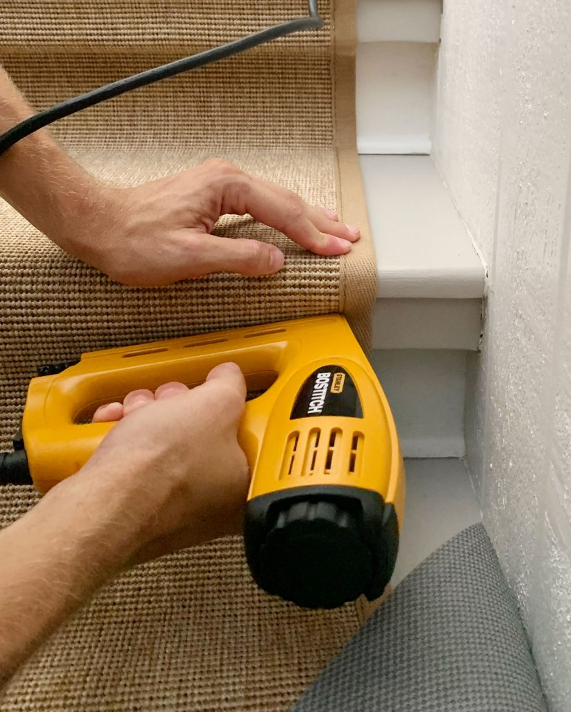 Yellow Electric Stapler Attaching Runner Under Lip Of Stair Tread