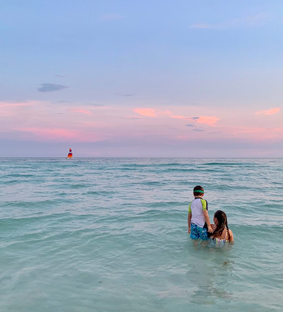 Kids playing in Gulf of Mexico at sunset with sailboat in background
