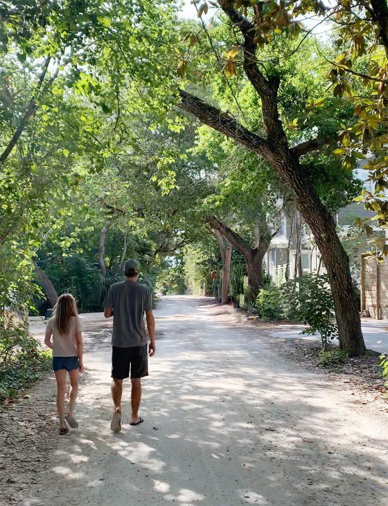 John and daughter walking in tree covered neighborhood