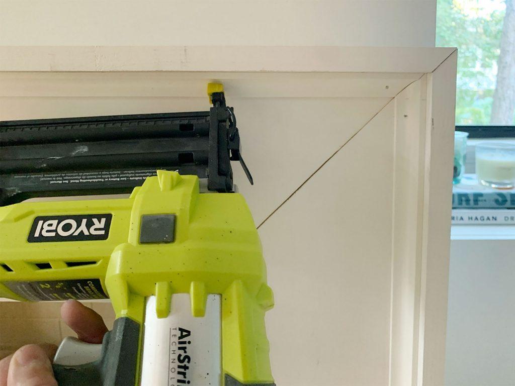 Nail Gun Securing Small Corner Trim Piece Along Inside Edge Of Mantel