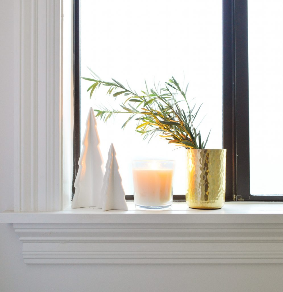 White Ceramic Trees With Candle And Gold Vase On Bathroom Window Sill