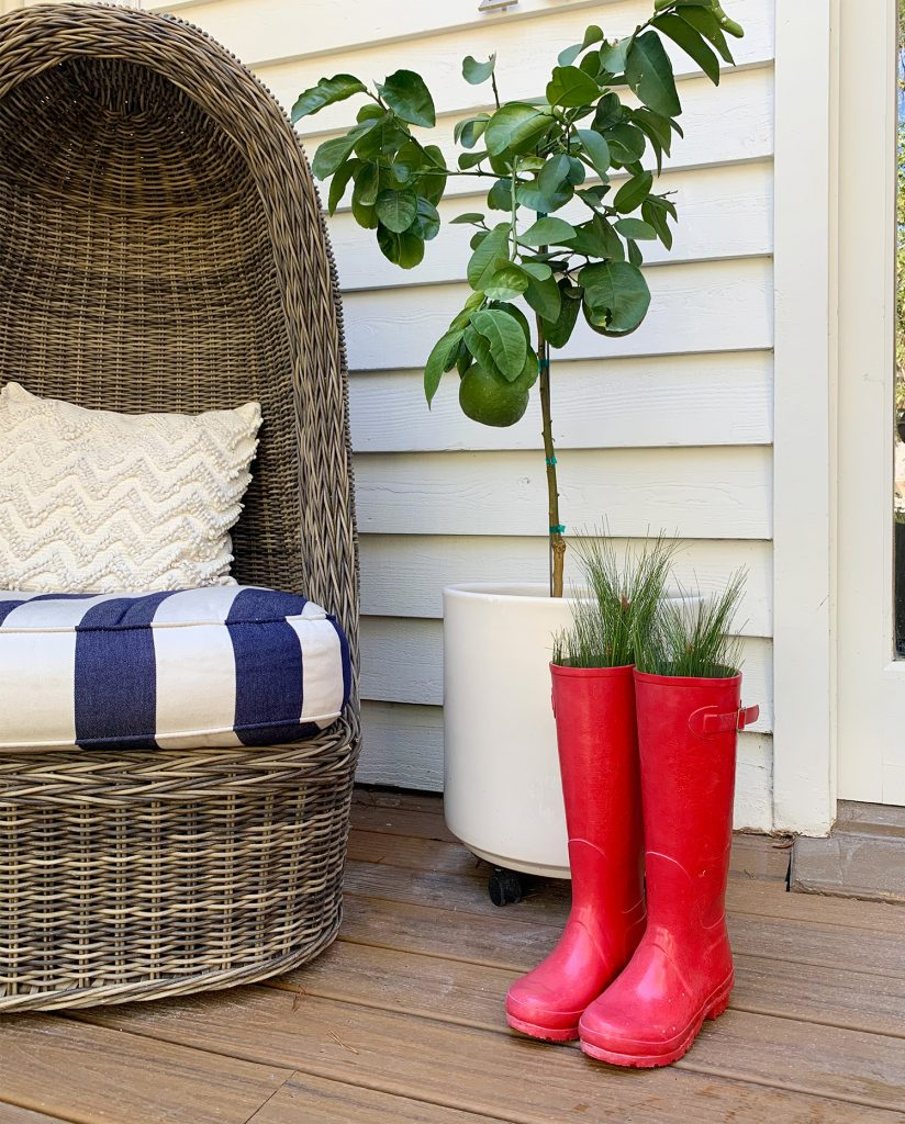 Red Boots With Holiday Greenery On Front Porch