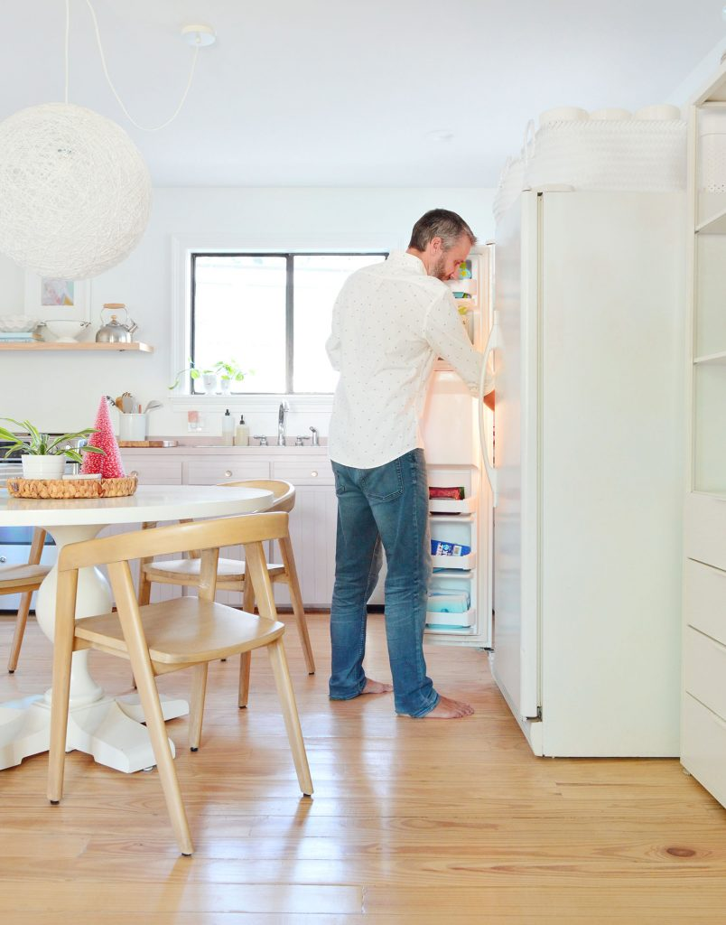 John standing with freezer door open next to round table in kitchen