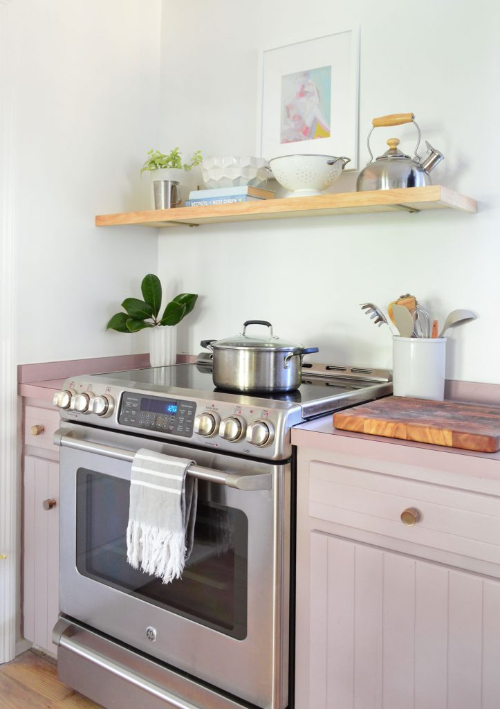 Stainless steel electric stove with mauve cabinets and floating wood shelf